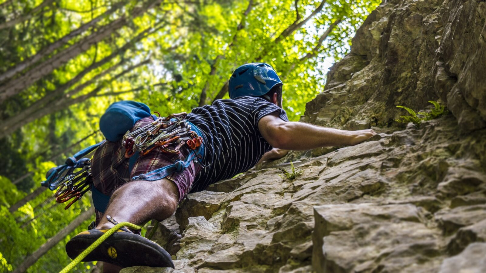 A rock climber on the rock face near their Killington condo rental